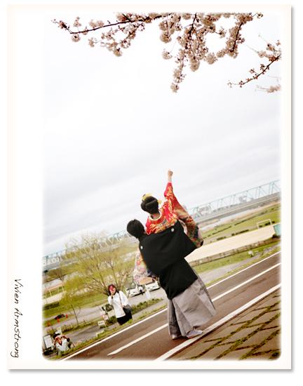 河原で記念撮影。桜とガッツポーズ