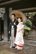 東京の撮影できる日本庭園で、ウェディングフォトを撮る和傘を持つ和装の新郎と色打掛を着た新婦