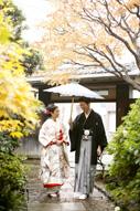 東京の撮影できる日本庭園で、紅葉の季節にウェディングフォトを撮る和傘を持つ和装の新郎とエスコートされる色打掛を着た新婦