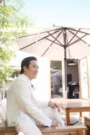 ご結婚式前にカフェテラスで写真撮影をする新郎さま