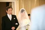 ご結婚式にてお父様とバージンロードを歩く新婦さま