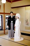 東京のウェディングフォトが撮影できる料亭で、和装の新郎と並ぶ綿帽子に白無垢姿の新婦