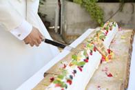 大きなノエル型ウェディングケーキにおふたりでケーキ入刀