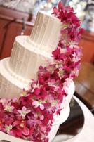 赤いかわいいお花があしらわれた3段のビックなウェディングケーキ