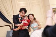 赤ちゃんと写真を撮る新郎新婦様