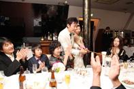 挙式当日の会食中の新郎新婦のキャンドルサービス中のドキュメンタリースナップ