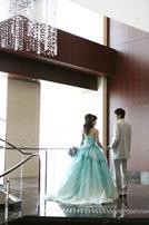 淡いブルーのカラードレスにお召替えした新婦さまと新郎さまのバックショット