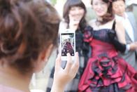 携帯電話でカラードレスのご新婦さまとご友人を撮影するゲストの方