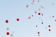 願いを込めて結婚式会場から青空に飛んでいく風船