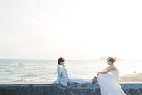 海を背景に、防波堤でくつろぐフォトウェディングを挙げるタキシードを着た新郎とウェディングドレスの新婦