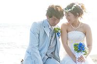 海を背景にフォトウェディングを挙げる、タキシードの新郎と、生花ブーケを持つウェディングドレスの新婦