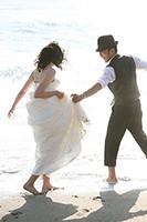 海でカジュアルなフォトウェディングを撮る、ラフにスーツを着る新郎と、ウェディングドレスを着る新婦