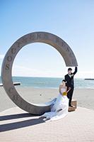青い空と海を背景に、海岸にあるモニュメントと一緒に写真を撮るタキシードの新郎とウェディングドレスの新婦のフォトウェディング