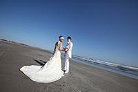 青空と海を背景に、海岸で見つめあうタキシード姿の新郎と、ウェディングドレスの新婦の、ウェディングフォト