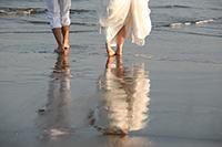 海岸で、裸足で水面を歩くカジュアルな新郎新婦のウェディングフォトのドラマチックな雰囲気のイメージカット