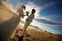 海岸で朝日の逆光の中、見つめあう新郎新婦のドラマチックなウェディングフォト