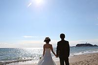 キラキラの太陽と海、青い空を、手をつなぎながら見つめる後ろ姿の新郎新婦のウェディングフォト