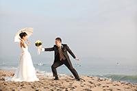 海岸で、日傘をさすドレス姿の新婦に、ブーケを持ったタキシードの新郎が、告白するウェディングフォト