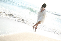 海岸でドレスが汚れないように持ち、カジュアルなウェディングフォトを撮る自然体な新婦の後ろ姿