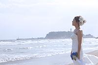 海岸で、ウェディングフォトを撮る、生花ブーケを持つドレス姿の新婦の写真