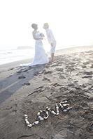 砂浜に「LOVE」のオーナメントを置いて、告白するウェディングフォトのシーンを撮る新郎新婦