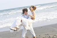 海岸でウェディングドレスを着る新婦を、お姫様抱っこする新郎の、ウェディングフォト