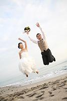 波打ち際で、カジュアルなスーツとドレスを着た新郎新婦の、ジャンプした瞬間を撮った個性的な写真