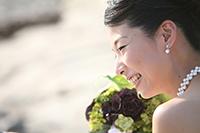 海岸のロケーションフォトで、自然な笑顔を見せる、ウェディングドレスを着た新婦のウェディングフォト