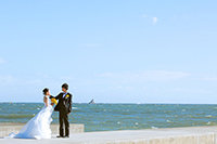 きれいな青空と海を背景に、ひまわりのブーケを持ったウェディングドレスの新婦と、タキシードを着た新郎のウェディングフォト