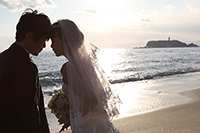 夕暮れの海岸で、ドラマチックなウェディングフォトを撮る、タキシードを着た新郎とウェディングドレスの新婦