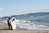 波打ち際で仲良く散歩しながら海でウェディングフォトを撮る、タキシードを着た新郎とウェディングドレスの新婦
