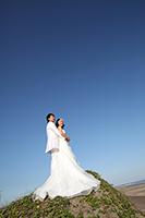 きれいな青空と海岸を背景に、仲良くウェディングフォトを撮るタキシードを着た新郎とウェディングドレスを着た新婦