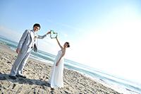 海岸でフォトウェディングを撮る、タキシードを着た新郎と、ウェディングドレスを着た新婦