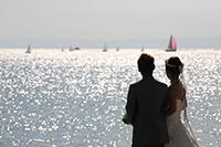 キラキラの海を眺めるドレスとタキシードをきてロケーション前撮りをする新郎新婦