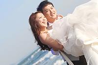 海を背景にドレスとタキシードをフォトウェディングをする新郎新婦