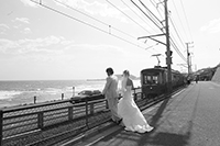 江ノ電を眺めて海のロケーション撮影をする新郎新婦