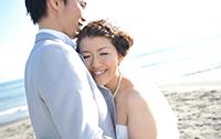 湘南の砂浜でドレスとタキシードで海ロケーションの前撮りをする新郎新婦