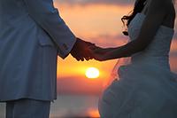 江ノ島の夕日と海を背景に手を繋いでフォトウェディングをする新郎新婦