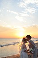 江ノ島の夕日と海を背景にフォトウェディングをする新郎新婦