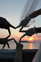 江ノ島の夕日と海を背景に手で星形を作る演出でフォトウェディング
