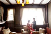旧細川侯爵邸の逆光がきれいな居間で和装の婚礼前撮り写真を撮る新郎と赤い色打掛を着た新婦