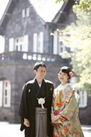 旧古河庭園洋館の外観を背景に明るい日差しのもと和装の婚礼前撮り写真を撮る新郎と緑色の打掛を着た新婦のツーショット