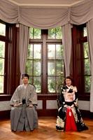 旧前田侯爵邸で自然光の入る明るい居室で並んで座るグレーの紋付き袴を着た新郎と黒引き振袖を着る新婦の和装婚礼前撮り写真