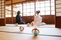 和装の婚礼前撮りフォトで畳のある和室の縁側で紙風船で遊ぶ新郎と白無垢の新婦