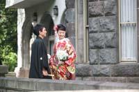 旧細川侯爵邸の石造りのバルコニーで和装の婚礼前撮りをする新郎と赤い色打掛を着た新婦