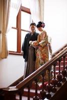 旧古河庭園洋館の自然光が入る階段で並んで立つ新郎と緑色の打掛を着た新婦の和装婚礼前撮り写真