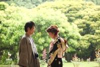 旧前田侯爵邸と新緑の美しい駒場公園で向かい合って和装の婚礼前撮り写真を撮るグレーの紋付き袴を着る新郎と黒引き振袖を着る新婦の写真