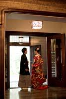 旧細川侯爵邸のエントランスで和装の婚礼前撮り写真を撮る新郎と赤い色打掛の新婦