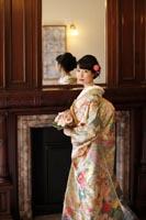 旧古河庭園洋館で和装の婚礼前撮り写真を撮る緑色の色打掛の新婦の一人の写真