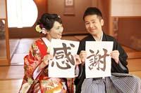 畳のある和室で和装の婚礼前撮りする感謝のメッセージカードを持つ新郎と赤い色打ちの新婦
